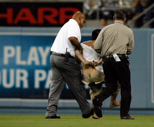 Security takes a man in to custody  after he ran on to the field at the conclusion of the Los Angeles Dodgers vs the Washington Nationals game at Dodger Stadium Saturday, July 26, 2008.  (Hans Gutknecht/LA Daily News)