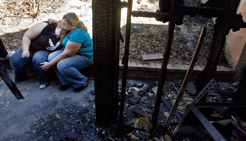 Melissa Salay , comforts daughter Tiffany Uzan, in the backyard of their home that was burned on Clymer St. in Northridge, Ca. The home caught fire when embers from the Sesnon Fire burning miles away got under the eaves of their home. The family lost most of their belongings to the fire and had to move in to a motel. The Boy Scouts of America have been providing assistance to the family. (Hans Gutknecht/Staff Photographer)