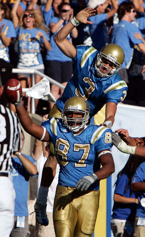 UCLA's Cory Harkey holds up the ball as quarterback Kevin Craft jumps on to his back after Harkey caught the game winning touchdown pass from Craft in the final seconds of their game against Stanford at the Rose Bowl in Pasadena CA. Saturday, October 18, 2008. UCLA defeated Stanford 23 to 20. (Hans Gutknecht/Daily News)