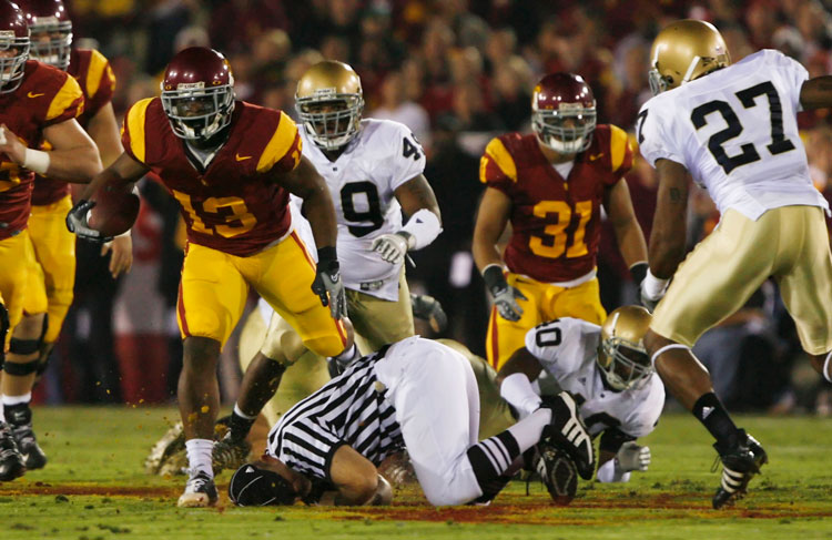USC'S Stafon Johnson #13 knocks an official to the ground as he carries the ball in the first quarter against Notre Dame during their game at the Los Angeles Memorial Coliseum in Los Angeles, Ca. Saturday, November 29, 2008. (Hans Gutknecht/Staff Photographer)