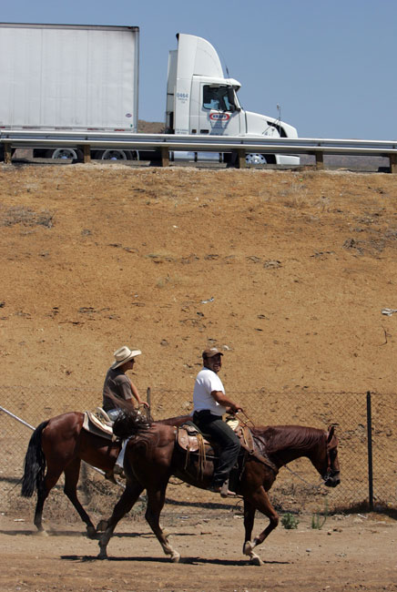 A group of horseback riders makes their way across Foothill Blvd. as traffic  drives on the 210 freeway above them in Sylmar Wednesday July 22, 2009. (Hans Gutknecht/LA Daily News)