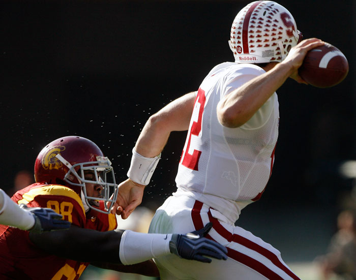 Stanford quarterback Andrew Luck #12 escapes the tackle of USC defensive tackle DaJohn Harris #98 during their Pac 10 Conference game at the Los Angeles Memorial Coliseum in Los Angeles,CA Saturday, November 14, 2009. Stanford beat USC 55-21. (Hans Gutknecht/LA Daily News)