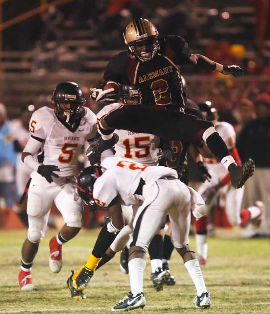 Alemany High School' Malcolm Marable #2 hurdles Dominguez High School's Aaron Williams #2 on a big gain in the 4th quarter during their CIF playoff football game at Alemany in Mission Hills. (Hans Gutknecht/LA Daily News)