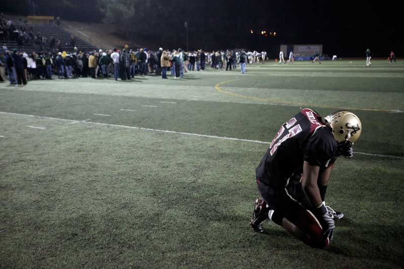 Alemany High School's Akeem Gonzales bows his head after  Mira Costa High School defeated his team to win the CIF-SS Western Division football final at College of Canyons in Santa Clarita.    (Hans Gutknecht/Staff Photographer)