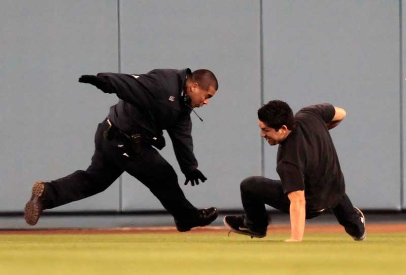 Los Angeles Dodgers security tackles a man after he ran on to the field during the Dodgers Pirates game at Dodger Stadium in Los Angeles Thursday, April 29, 2010. (Hans Gutknecht/Staff Photographer)
