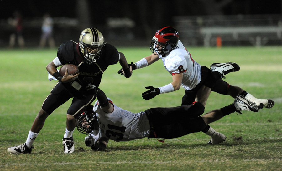 Alemany's Vernon Adams #3 scrambles as  Harvard Westlake defenders move in during their game at Alemany High School Friday, October 1, 2010. (Hans Gutknecht/Staff Photographer)