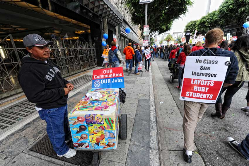 A street vender looks for customers on South Olive St. as protesters march their way from the Los Angeles Convention Center to a rally at Pershing Square to show support for unions to have the right to collective bargaining. (Hans Gutknecht/Staff Photographer)